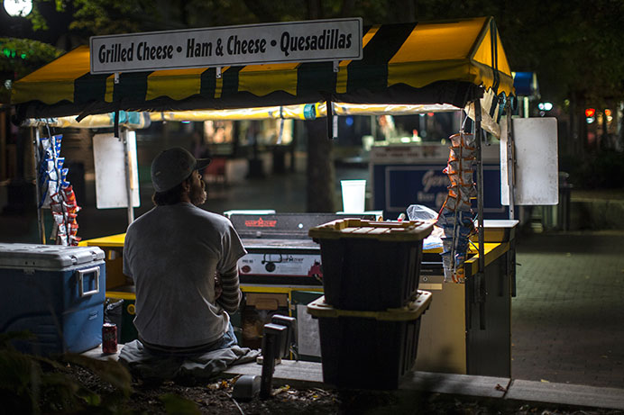 Ted Taylor sits behind Marco's Grilled Cheese Cart on Wednesday, Oct. 14, 2015. Taylor has worked at the cart for six months. (The Daily Iowan/Sergio Flores)