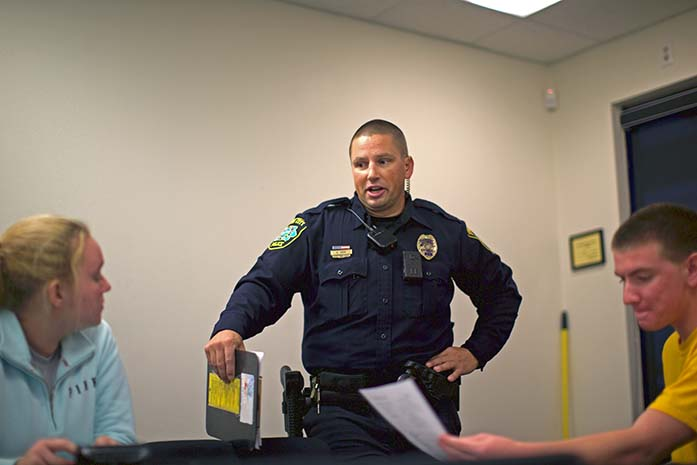 Iowa City police officer Rob Cash talks with Police Explorer members inside the Iowa City Police Department substation on Oct. 28, 2015. Police Explorers is a program for high school students interested in police work and assisting with community activities and projects. (The Daily Iowan/Brooklynn Kascel)