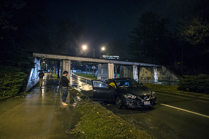 A man directs traffic around his friend's stalled car on Wednesday, Nov. 11, 2015. Heavy rainfall and flash flooding caused the car to stall as he drove down the street.
