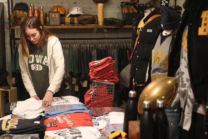 Employee at Tailgate Samantha Peterson organizes clothes in the Tailgate clothing store near the intersection of Clinton St. and Washington St. on Tuesday, Dec. 8, 2015. Tailgate first opened June of 2014. (The Daily Iowan/Joshua Housing)