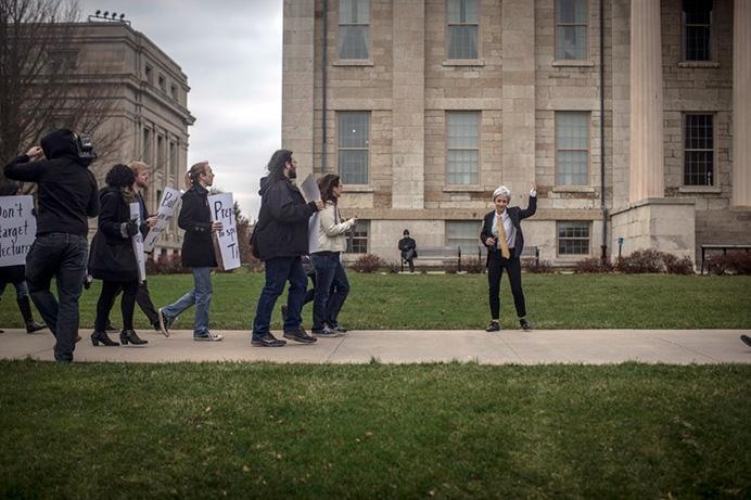 """Carleen Maur leads a group of protesters to UI President Bruce Harreld's office on Thursday, Dec. 17 2015.  After the offhanded comment, """"all unprepared lectures should be shot"""", was made by Harreld in a staff meeting last week, members of the community organized a protest. (The Daily Iowan/Jordan Gale)"""