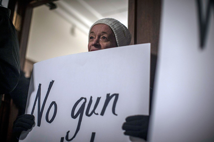 """Protesters hold signs outside the president's office on, Thursday Dec 17, 2015. This protest against the president comes after a controversial """"should be shot"""" comment during a recent Staff Council Meeting. (The Daily Iowan/Jordan Gale)"""