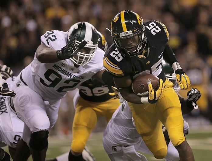 Iowa running back Akurm Wadley tries to avoid a tackle during the Big Ten Championship against Michigan State in Lucas Oil Stadium in Indianapolis on Saturday, Dec. 5, 2015. The Spartans defeated the Hawkeyes in the last seconds of the game, 16-13. (The Daily Iowan/Margaret Kispert)