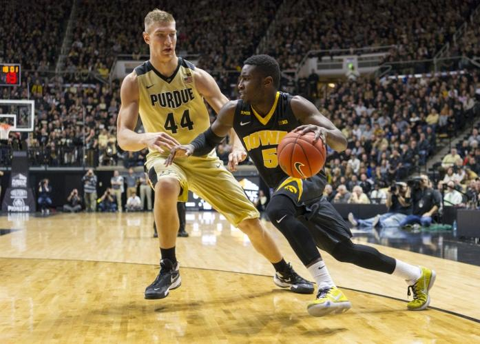 Iowa guard Anthony Clemmons (5) drives the ball along the baseline as he's defended by Purdue center Isaac Haas (44) during the first half of an NCAA college basketball game, Jan. 2, 2016, in West Lafayette, Ind. (AP Photo/Doug McSchooler)