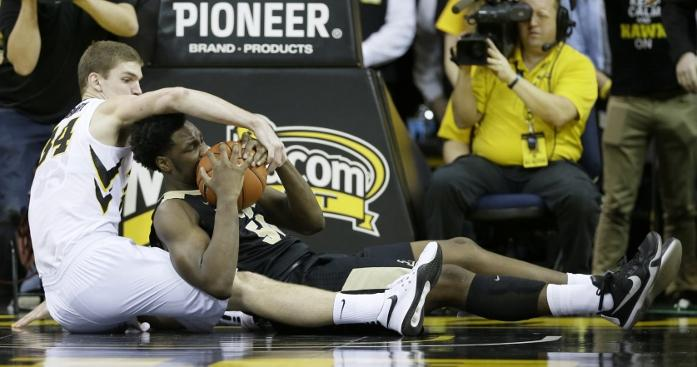 Iowa center Adam Woodbury, left, fights for a loose ball with Purdue forward Caleb Swanigan during the first half of an NCAA college basketball game, Sunday, Jan. 24, 2016, in Iowa City, Iowa. (AP Photo/Charlie Neibergall)
