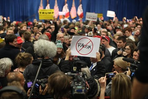 A protester raises a sign against Donald Trump at the University Field House before Trump came out to speak on Tuesday, Jan 26, 2016. Through out the event multiple people were escorted out for protesting against Donald Trump's campaign. (The Daily Iowan/Jordan Gale)