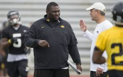 Iowa Hawkeyes head coach Kirk Ferentz  talks with graduate assistant Kelvin Bell during the team's 13th Outback Bowl Practice Saturday, Dec. 28, 2013 as they prepare to face the LSU Tigers in Tampa.  (Brian Ray/hawkeyesports.com)