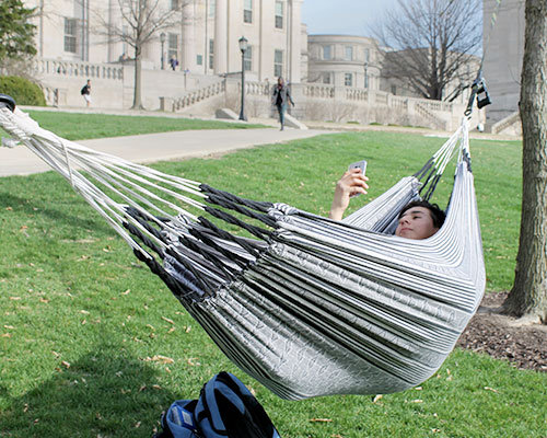 Student Pablo A Suarez Beltran enjoys the warm weather in his hammock on the Pentacrest on Tuesday, March 29. It is supposed to be 50 degrees throughout the rest of the week. (The Daily Iowan/McCall Radavich)