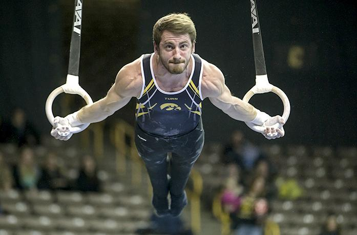 Jack Boyle performs on the rings inside Carver Hawkeye Arena on Saturday, Jan. 24, 2015. Iowa defeated UIC in their home opener 428.600 to 398.600. (The Daily Iowan/Sergio Flores)