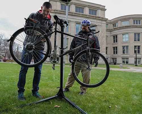 World of Bikes staff member Bryan Wenszel provides a free tune up as part of Spring Bike Tune-up Day on the Pentacrest at The University of Iowa on Friday, April 1, 2016. Staff from the World of Bikes offered free tune ups to riders in celebration of Earth Month. (The Daily Iowan/Anthony Vazquez)