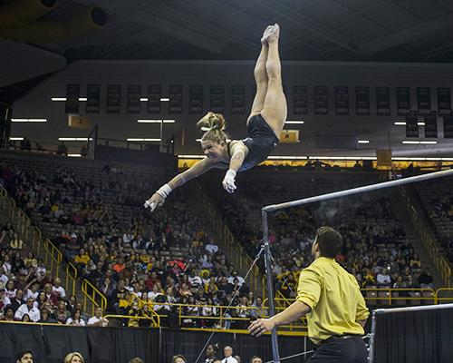Iowa gymnast Mollie Drenth swings off the bar at Carver Hawkeye, on Saturday, Apr 2, 2016. Iowa took 4th place, scoring total of 195.450 for team score. (The Daily Iowan/Peter Kim)