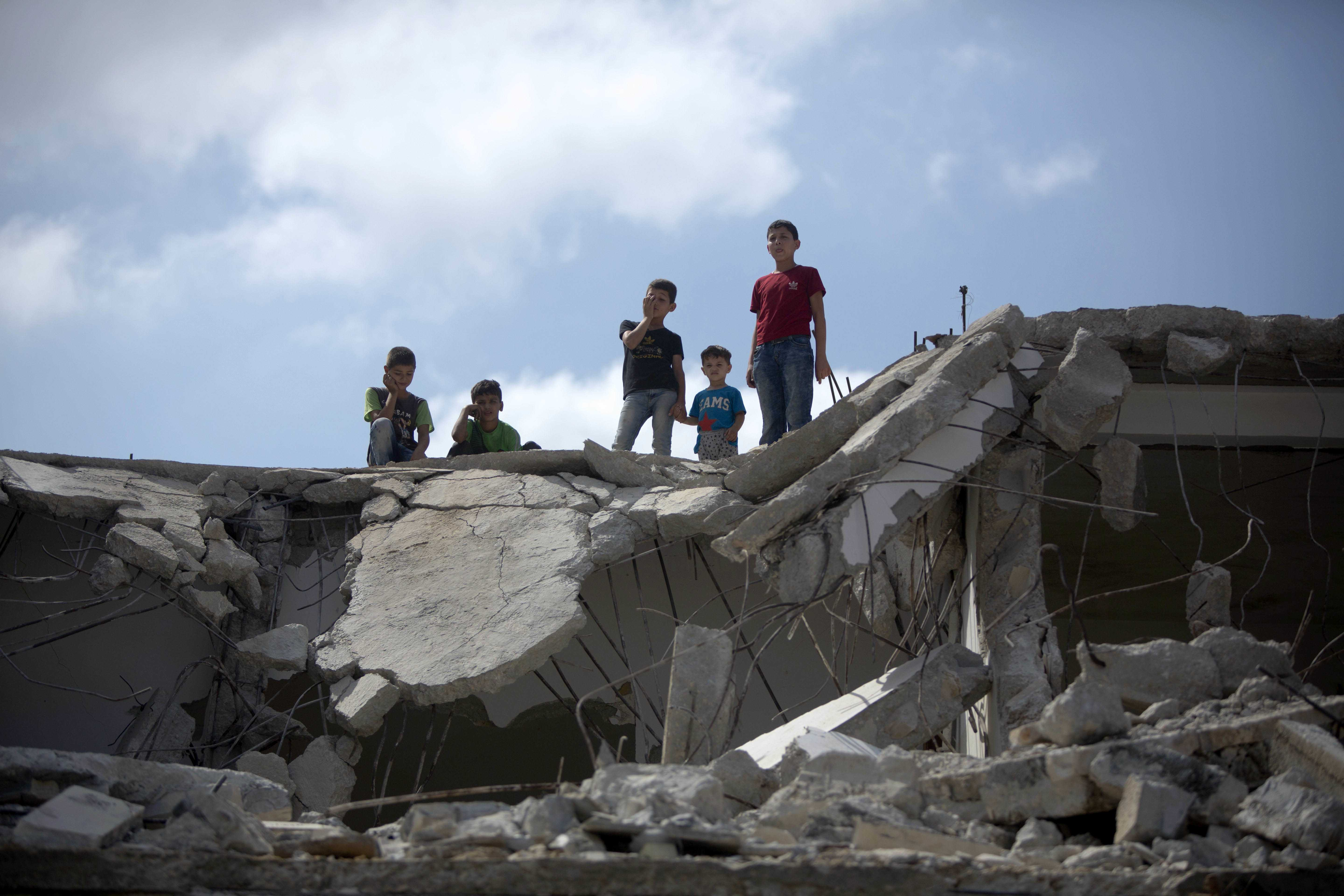 Palestinians boy stand amidst the rubble the house of Bilal Abu Zeid that was demolished by the Israeli army in the West Bank village of Kabatiya, near Jenin, Monday, July 18, 2016. Abu Zeid is said by the army to have been involved in an attack in Jerusalem in February that killed an Israeli paramilitary police officer. The military did not disclose what role Abu Zeid allegedly played in the attack.(AP Photo/Majdi Mohammed)