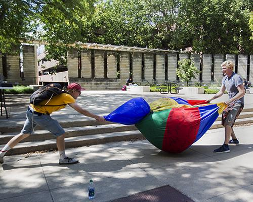 Zeta Beta Tau members Jared Bohlman and Nolan Lydolph deflate a beach ball along the T. Anne Cleary Walkway on Thursday September 1, 2016. The fraternity collected signatures from students as a fundraiser to support Children's Miracle Network. (The Daily Iowan/Vivian Le)