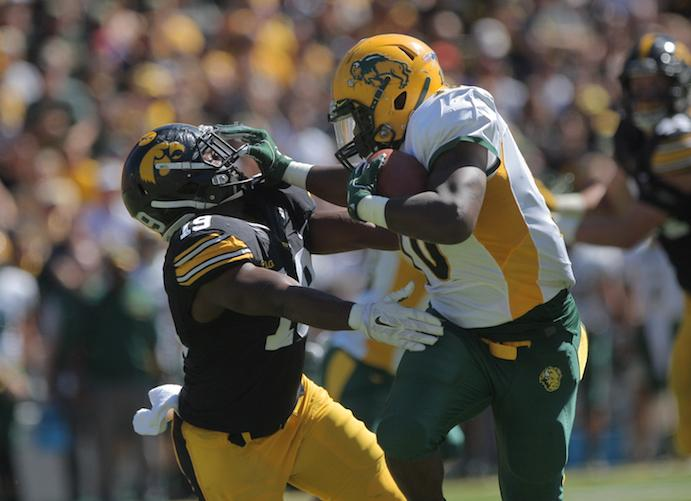 NDSU running back Lance Dunn stiff arms Iowa defensive back Miles Taylor during the Iowa-NDSU game at Kinnick on Saturday, Sept. 17, 2016. NDSU defeated Iowa in the final seconds of the game with a 37-yard field goal, 23-21. (The Daily Iowan/Margaret Kispert)