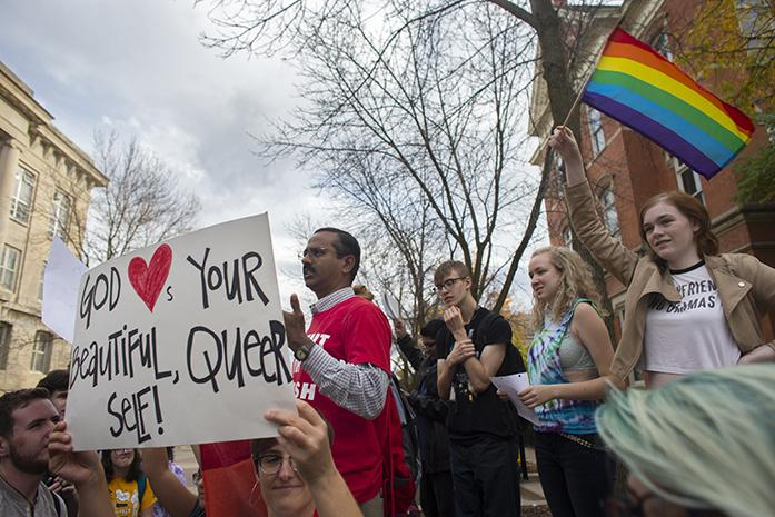 UI freshman Josie Bratt waves a LGBTQ pride flag while protesters surround a street preacher on the T. Anne Cleary Walkway on Wednesday, October 19, 2016. Protesters chanted and played pro-LGBTQ music to combat street preaching which aligns with University of Iowa's LGBTQ history week. (The Daily Iowan/Joseph Cress)