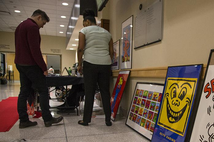 UI senior Brittany Coneyers greets guests near the Kendal Gallery while showcasing art from Keith Haring in the IMU on Wednesday, Nov. 30, 2016. IC Red Week had an informational table with condoms, snacks, and photo frames for guests to pose for a photo. (The Daily Iowan/Joseph Cress)