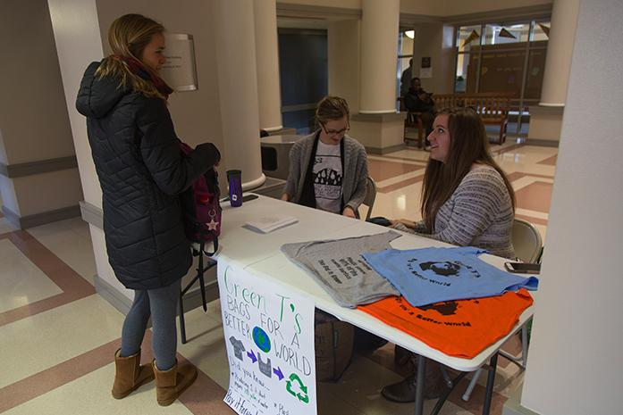 Madelyn Putman and Amy Schembari help a fellow student as she picks up a bag made from a recycled shirt at the Pappajon Business Building, in Iowa City, Iowa  on Tuesday, Dec. 6, 2016. Green Tees: Bags for a Better World is an initiative from the Office of Sustainabiltiy in which they collect unwanted t-shirts from friends and family and transformed them into reusable shopping bags. (The Daily Iowan/Anthony Vazquez)