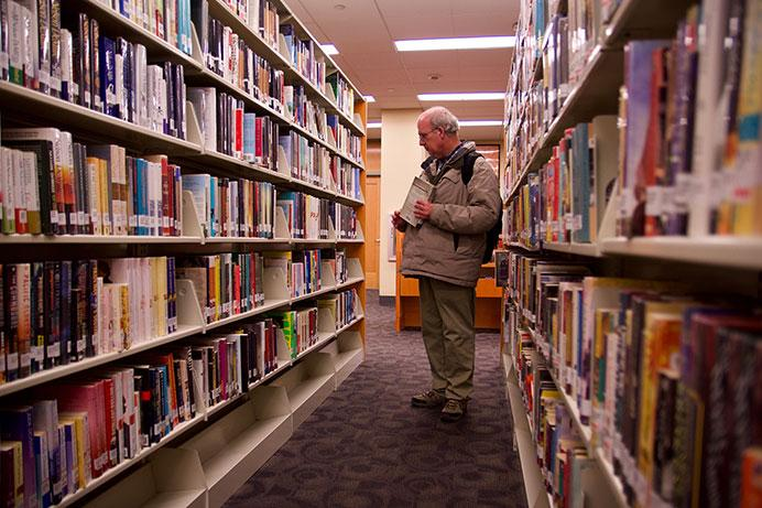 Joseph+McKenna+stands+in+the+fiction+section+of+the+Iowa+City+Public+Library+earlier+this+year.+The+library+was+established+in+1896.+%28The+Daily+Iowan%2FOlivia+Sun%29