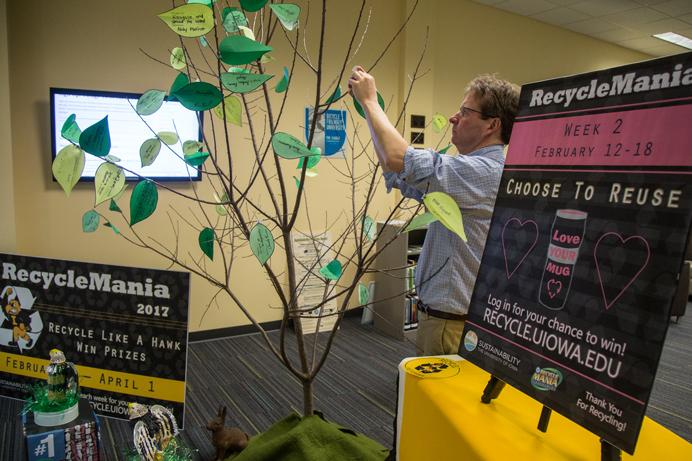 George McCrory of the Sustainability program at Iowa places a leaf on one of the branches. Leaves mark a pledge for an indidivual to do their part improving their recycling habit, in the Sustainability Office in Iowa City, Iowa on Tuesday, Feb. 14, 2017. Recylemania is an national competition which encourages universities to promote and take action in recycling. (The Daily Iowan/Anthony Vazquez)