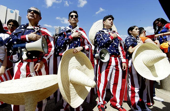 Julio Arellano, left, stands for the pledge of allegiance with his children from left, Israel Arellano, Julio C. Arellano and Brisa Arellano during a protest rally downtown Dallas, Sunday, April 9, 2017. Thousands of people are marching and rallying in downtown Dallas to call for an overhaul of the nations immigration system and end to what organizers say is an aggressive deportation policy. (AP Photo/LM Otero)