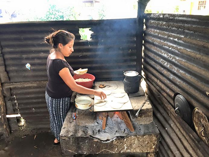 A woman uses a corn mix and water to make tortillas for her family in El Porvenir, Guatemala on an aged stove. (The Daily Iowan/Grace Pateras)