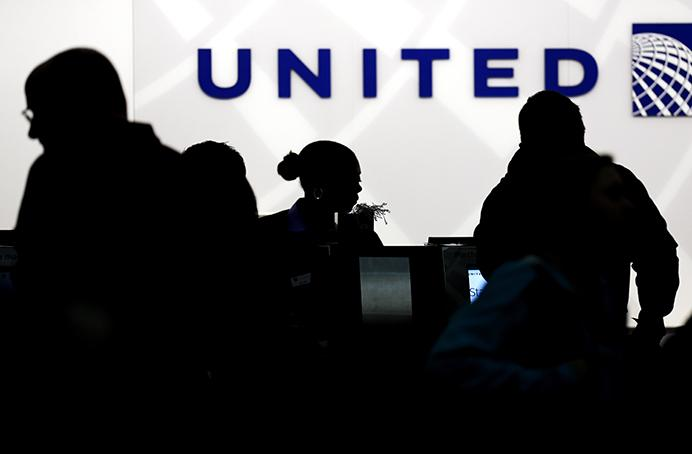 FILE - In this Saturday, Dec. 21, 2013, file photo, travelers check in at the United Airlines ticket counter at Terminal 1 in OHare International Airport in Chicago. After a man is dragged off a United Express flight on Sunday, April 9, 2017, United Airlines becomes the butt of jokes online and on late-night TV. Travel and public-relations experts say United has fumbled the situation from the start, but it's impossible to know if the damage is temporary or lasting. Air travelers are drawn to the cheapest price no matter the name on the plane. (AP Photo/Nam Y. Huh, File)
