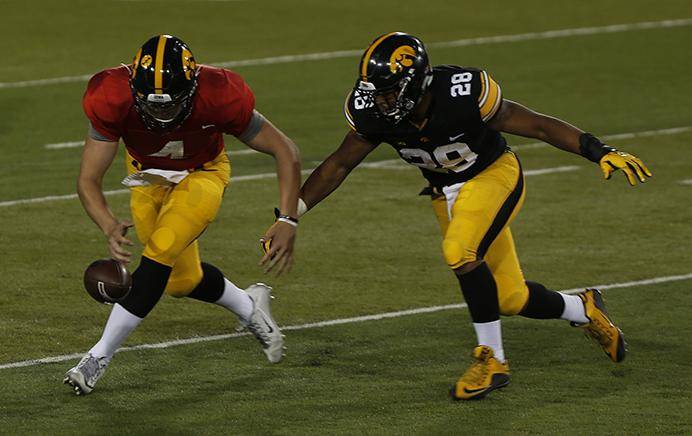 Iowa+quarterback+Nathan+Stanley+and+running+back+Toren+Young+reach+for+a+bobbled+snap+during+the+spring+game+at+Kinnick+Stadium+on+Friday%2C+April+21%2C+2017.+Gervase+had+three+total+interceptions+leading+the+defense+to+a+63-47+victory+over+the+offense.+%28The+Daily+Iowan%2F+Alex+Kroeze%29