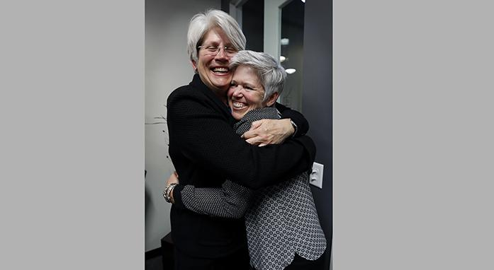 Jane Meyer, former senior associate athletic director at the University of Iowa, gets a hug from her partner Tracey Griesbaum, right, following a news conference, Thursday, May 4, 2017, in Des Moines, Iowa. A jury on Thursday awarded more than $1.4 million to Meyer ruling that the university had discriminated against her because of her gender and sexual orientation. (AP Photo/Charlie Neibergall)