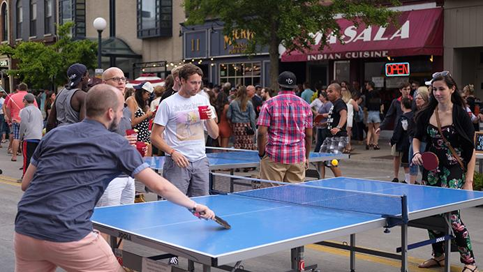 Partygoers play ping pong on Dubuque Street during the Iowa City Downtown District Block Party on Saturday June 25, 2017. The Block Party, hosted by the ICDD was the first use of Iowa Citys changed rules allowing open containers for select events downtown (Nick Rohlman/The Daily Iowan)