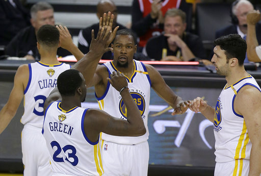 Golden State Warriors forward Kevin Durant, center, celebrates with guard Stephen Curry, top left, forward Draymond Green (23) and center Zaza Pachulia during the second half of Game 2 of basketballs NBA Finals against the Cleveland Cavaliers in Oakland, Calif., Sunday, June 4, 2017. (AP Photo/Ben Margot)