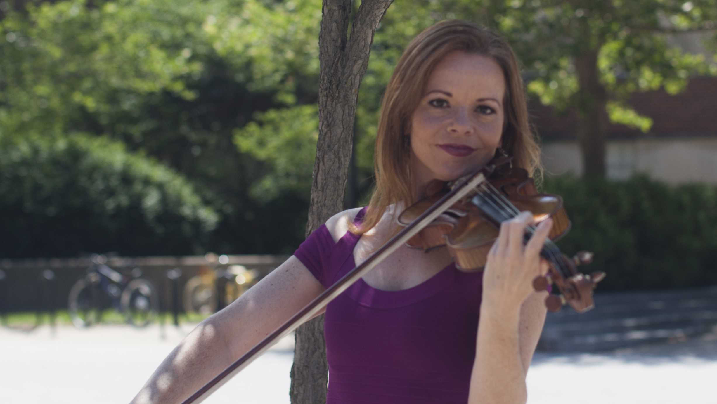 Lisa Dondlinger, a violinist and former Miss Iowa, plays her violin outside the Main Library. Dondlinger returned from Los Angeles to debut her first solo album. ( Hieu Nguyen/The Daily Iowan)