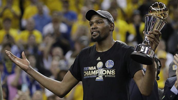 Golden State Warriors forward Kevin Durant gestures as he holds the Bill Russell NBA Finals Most Valuable Player Award after Game 5 of basketballs NBA Finals between the Warriors and the Cleveland Cavaliers in Oakland, Calif., Monday, June 12, 2017. The Warriors won 129-120 to win the NBA championship. (AP Photo/Marcio Jose Sanchez)