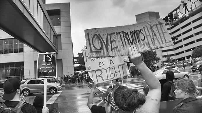 Anti-Trump protesters chant and display their signs within view of Pro-Trump supporters near the Donald Trump rally in Cedar Rapids, Iowa on Wednesday, June 21, 2017. The arena was filled to capacity and many of the supporters had to be turned away. (James Year/The Daily Iowan)