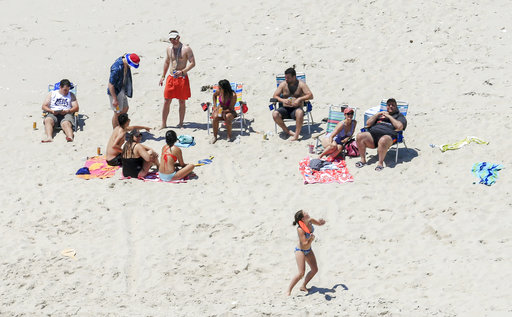 In this Sunday, July 2, 2017, photo, New Jersey Gov. Chris Christie, right, uses the beach with his family and friends at the governors summer house at Island Beach State Park in New Jersey. Christie is defending his use of the beach, closed to the public during New Jerseys government shutdown, saying he had previously announced his vacation plans and the media had simply caught a politician keeping his word. (Andrew Mills/NJ Advance Media via AP)