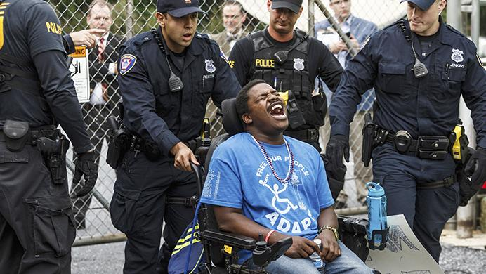 Brandon Ezekiel, with Philly Adapt, is arrested after blocking the entrance of ABC 27s studio in Harrisburg, Pa., in protest to the arrival of Sen. Pat Toomey for a TV Town Hall, Wednesday, July 5, 2017. (James Robinson /PennLive.com via AP)