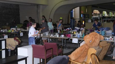 Shoppers sort through used kitchenware, clothing, and furniture during Rummage in the Ramp in the Chauncey Swan parking ramp on Wednesday, July 26, 2017. Rummage in the Ramp is put on annually by the city in order to reduce the mass of belongings abandoned on curbs and to raise money for a variety of nonprofit organizations. (Nick Rohlman/The Daily Iowan)