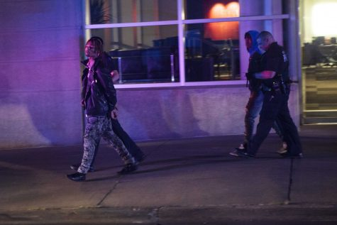 Iowa City police officers arrest and escort two individuals into cruisers outside Hotel Vetro early Sunday, Aug. 27. The police department responded to reports of shots fired downtown around 1:30 a.m. (Ben Smith/The Daily Iowan)