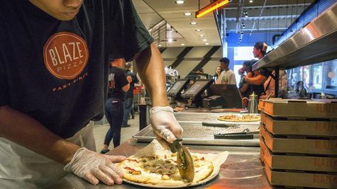 Iowa City resident and City High School senior, Abott Ruhinda, puts the finishing touches on a pie at Blaze Pizza on Sunday, Aug 20, 2017. Blaze has recently opened on the 17th and gave away free pizza as a promotional event the following friday. (James Year/Daily Iowan)