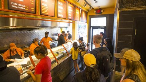 Community members wait in line in Pancheros on Tuesday. Pancheros has celebrated its 25th anniversary all month with promotions such as free queso on its anniversary and $1 burritos at its downtown location Tuesday. (Joseph Cress/The Daily Iowan)