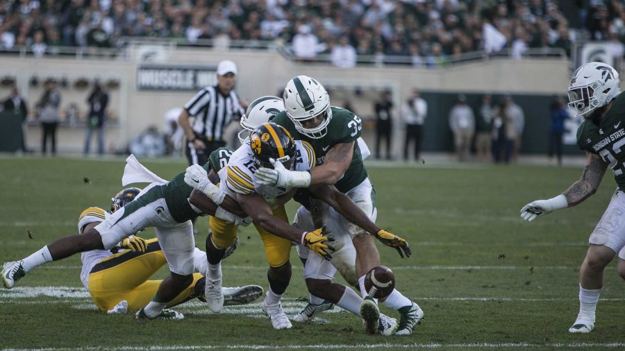 Iowa+wide+receiver+Brandon+Smith+%2812%29+attempts+to+recover+a+fumble+forced+by+Michigan+State%27s+Joe+Bachie+during+the+game+between+Iowa+and+Michigan+State+at+Spartan+Stadium+on+Saturday%2C+Sept.+30%2C+2017.+The+Hawkeyes+fell+to+the+Spartans+with+a+final+score+of+10-17.+%28Ben+Smith%2FThe+Daily+Iowan%29