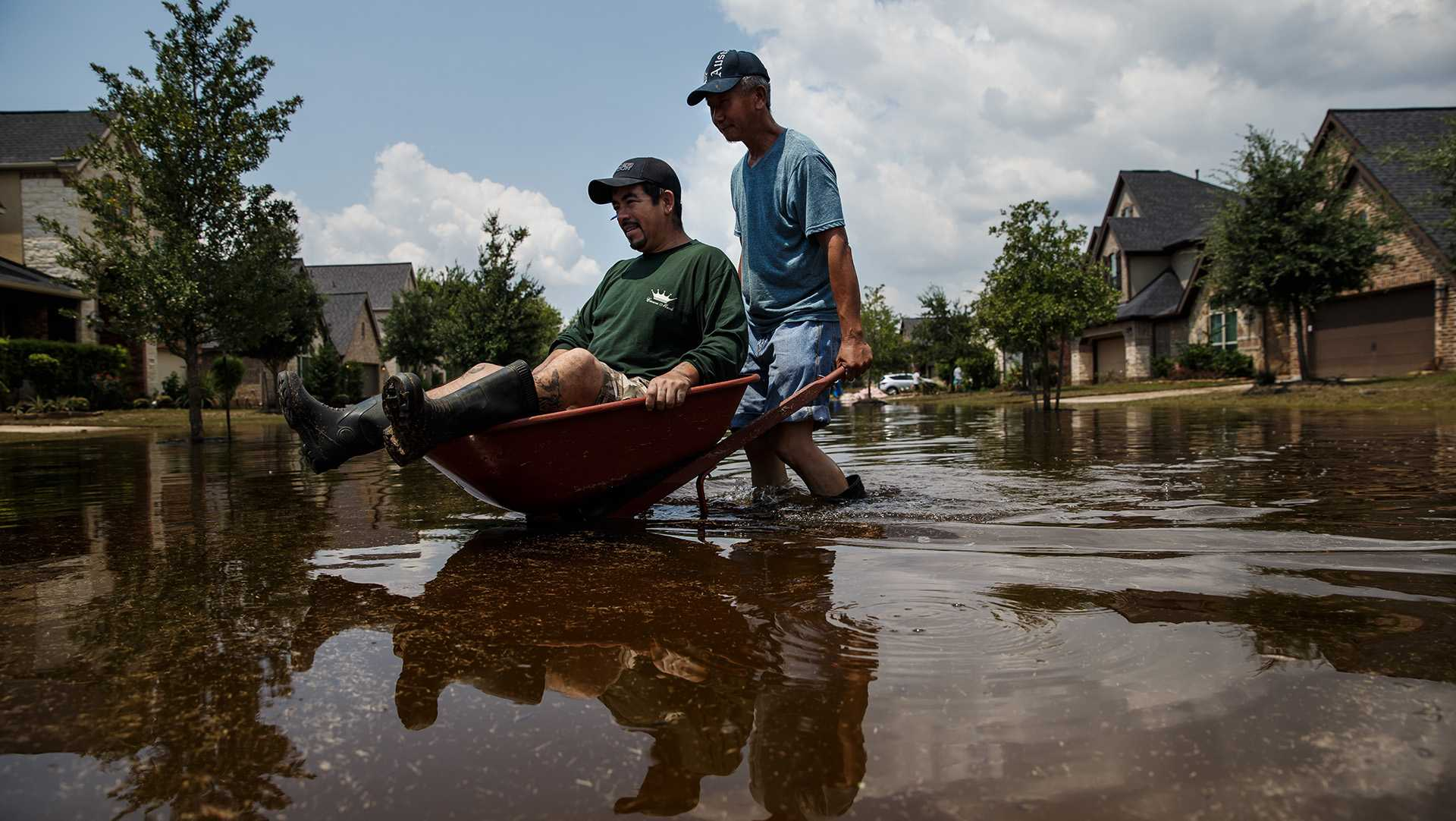 Lung Hui Chen pushes Manuel Terrazas in a wheelbarrow across flooded streets as local residents clear out damaged homes in the aftermath of Hurricane Harvey, in the Millwood subdivision of Fort Bend County, Texas, on Saturday, Sept. 2, 2017. (Marcus Yam/Los Angeles Times/TNS)