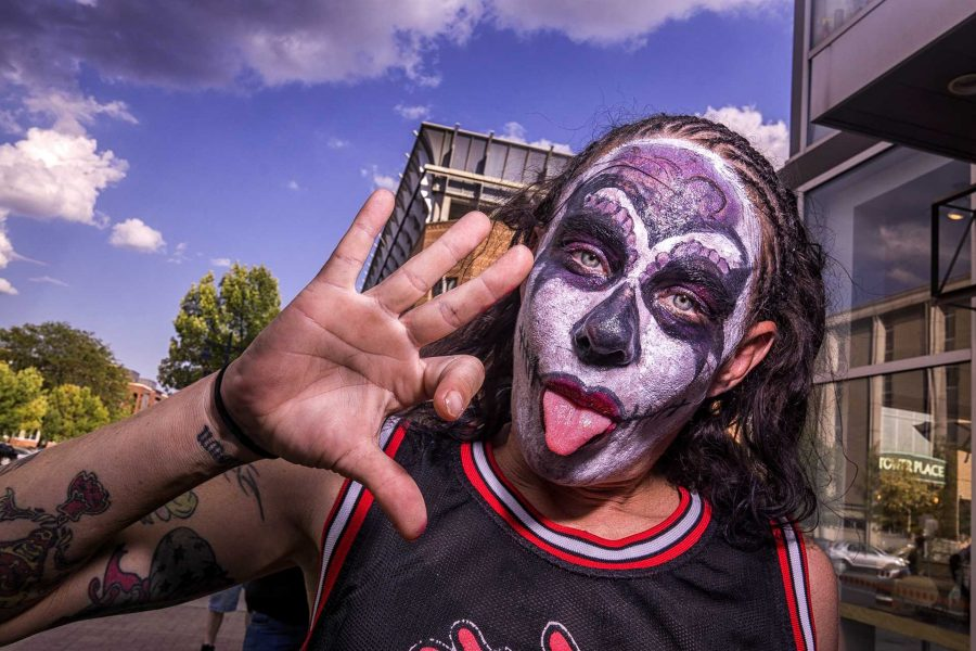 A Juggalette poses for a photograph while standing in line before the Insane Clown Posse concert on Saturday, Sept. 24, 2017. The sign she is displaying stands for WC or Wicked Clowns. (James Year/The Daily Iowan)