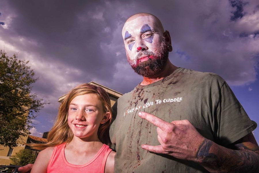 Sleepy the Juggalo and his daughter pose for a photo while waiting in line for the Insane Clown Posse concert at the Blue Moose on Saturday, Sept. 24, 2017. They both made the 1 hour drive from Manchester, Iowa to see the show and said he became an ICP fan for the energy, mutual respect and love. (James Year/The Daily Iowan)