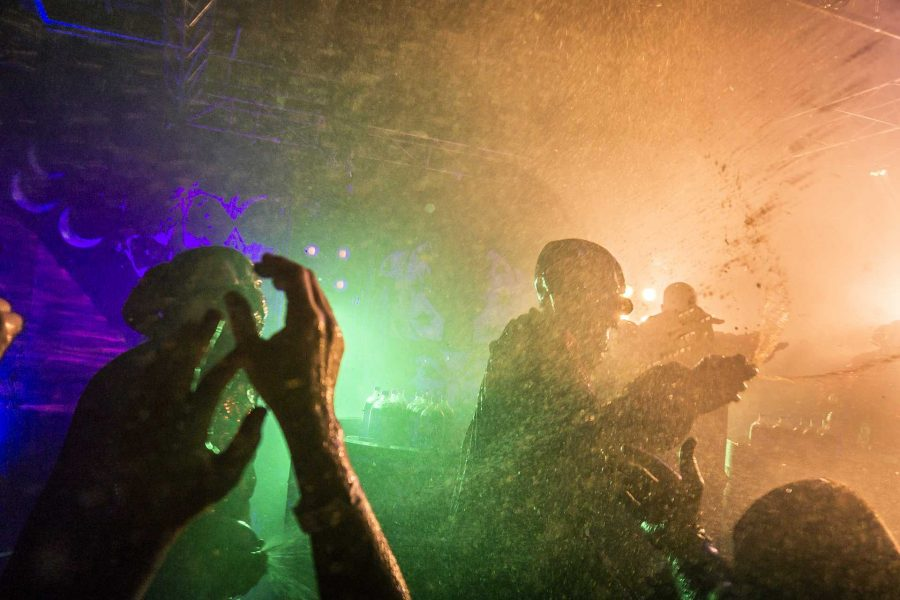 Backup performers dressed as clowns spray bottles of Faygo soda into an overheated crowd of Juggalos and concertgoers on Saturday, Sept. 23, 2017. On average ICP uses 350 two liter bottles of soda per event depending on the size of the venue. (James Year/The Daily Iowan)