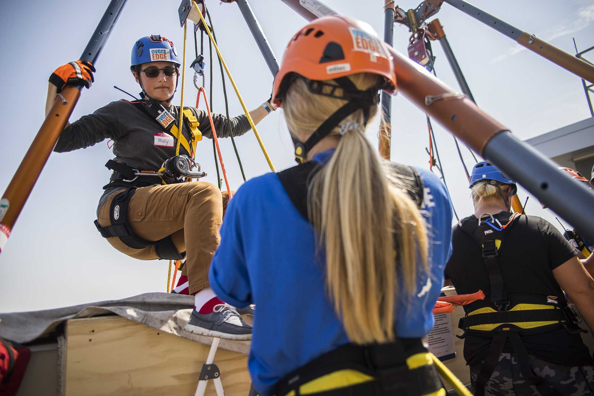 EPI reporter, Molly Hunter, prepares to repel down the side of the Hotel Vetro building at a Ronald McDonald House sponsored event on Friday, Sept. 15. Those who would like to participate could pay $25 for a spot on the list to repel. (Ben Smith/The Daily Iowan)