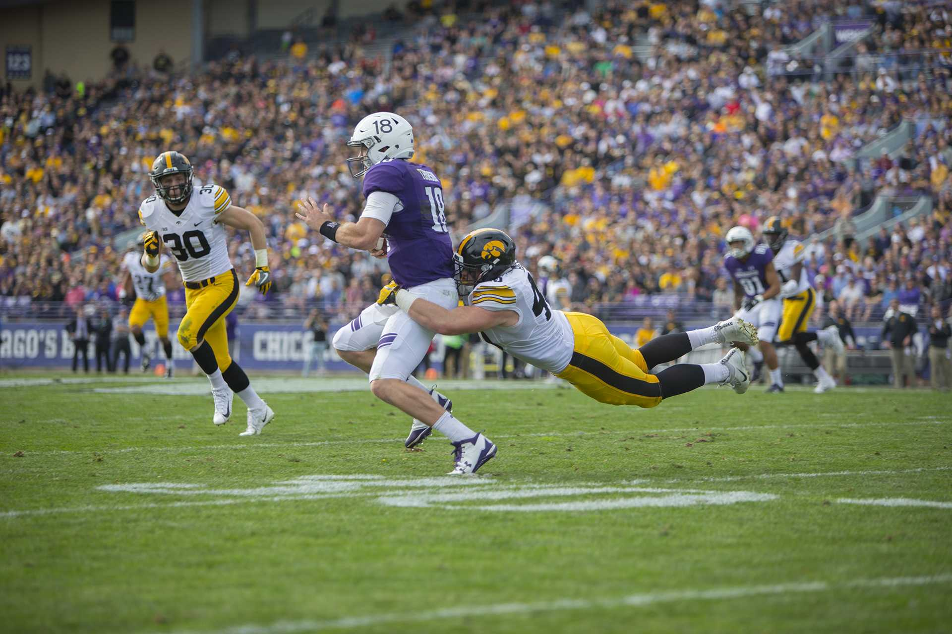 Iowa defensive end Parker Hesse tackles Northwestern quarterback Clayton Thorson during the game between Iowa and Northwestern at Ryan Field in Evanston on Saturday, Oct. 21, 2017. The wildcats defeated the Hawkeyes, 17-10, in overtime. (Lily Smith/The Daily Iowan)