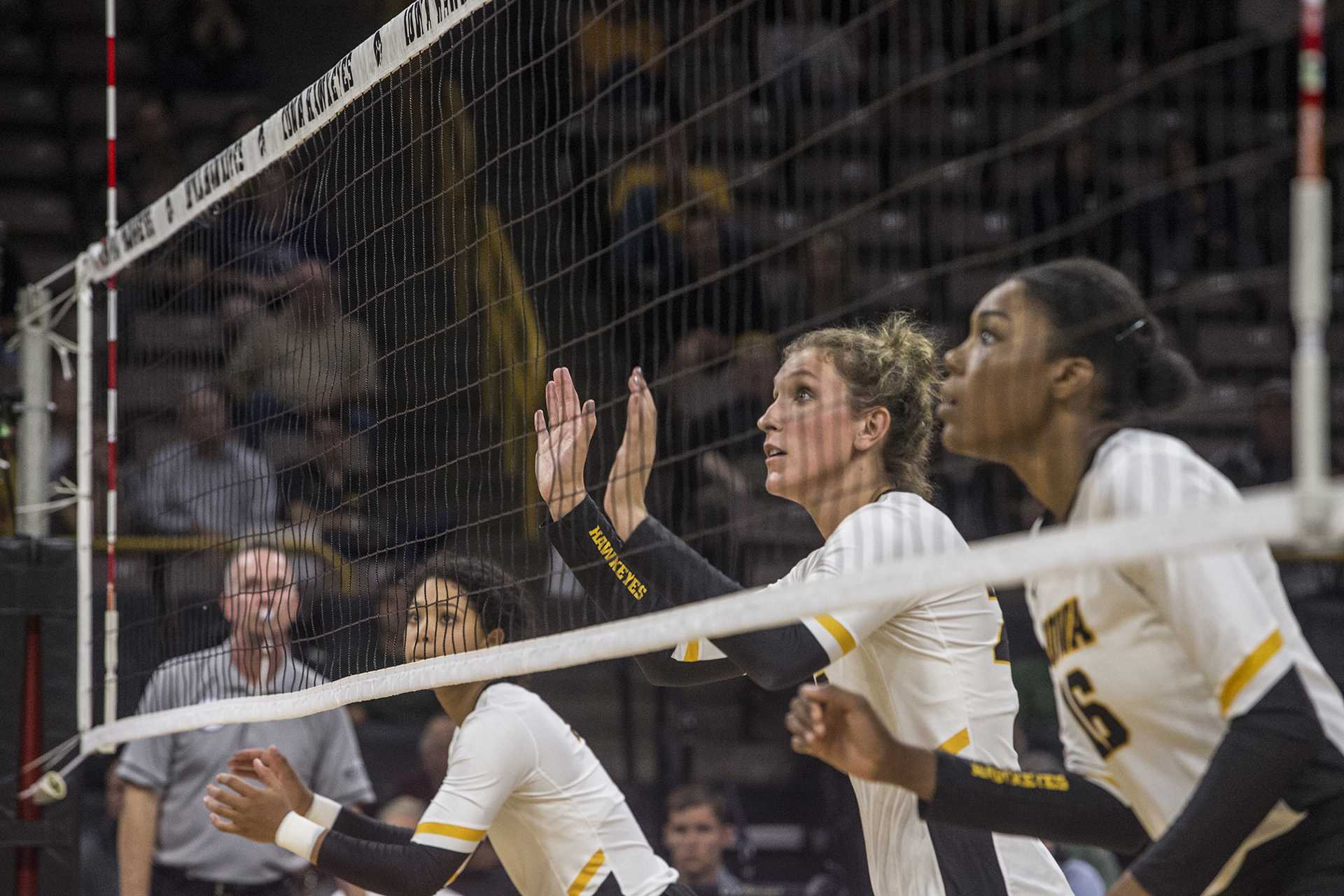 Iowa's Brie Orr, Jess Janota, and Taylor Louis prepare for the ball during a match against Michigan at Carver-Hawkeye Arena on Wednesday, Oct. 4, 2017. Iowa defeated Michigan 3 sets to 1. (Nick Rohlman/The Daily Iowan)