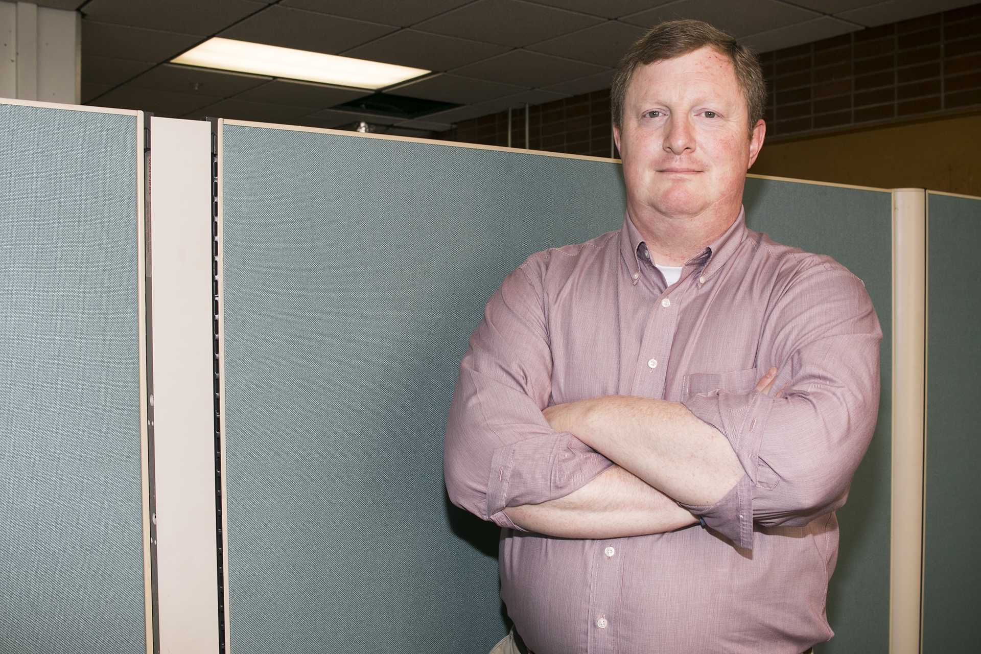 John Kenyon stands in his cubicle of the former DI newsroom in the Communication Center.