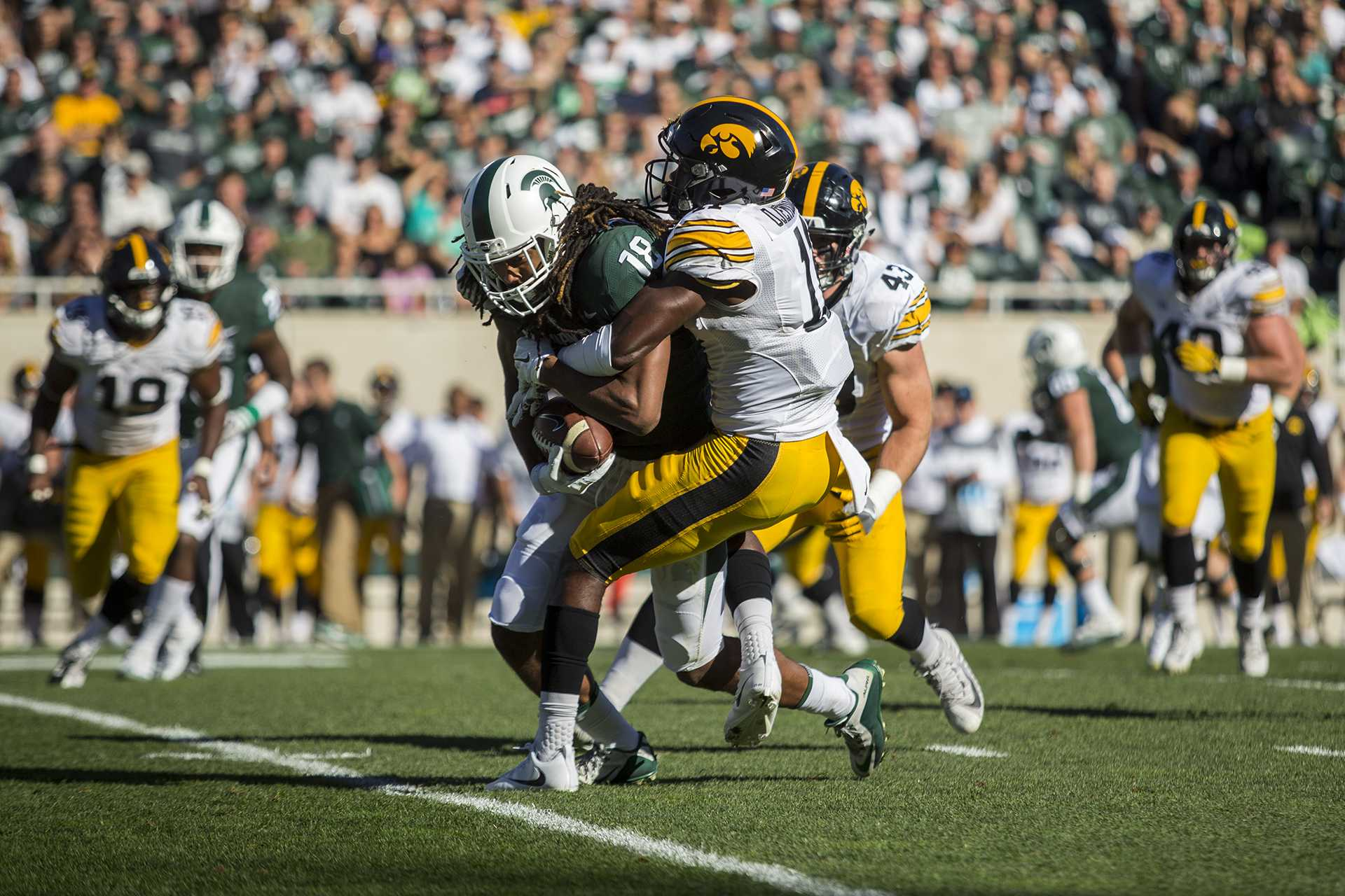 Iowa cornerback Michael Ojemudia tackles Michigan State wide receiver Felton Davis during the game between Iowa and Michigan State at Spartan Stadium on Saturday Sept. 30, 2017. The Spartans defeated the Hawkeyes 17-10.