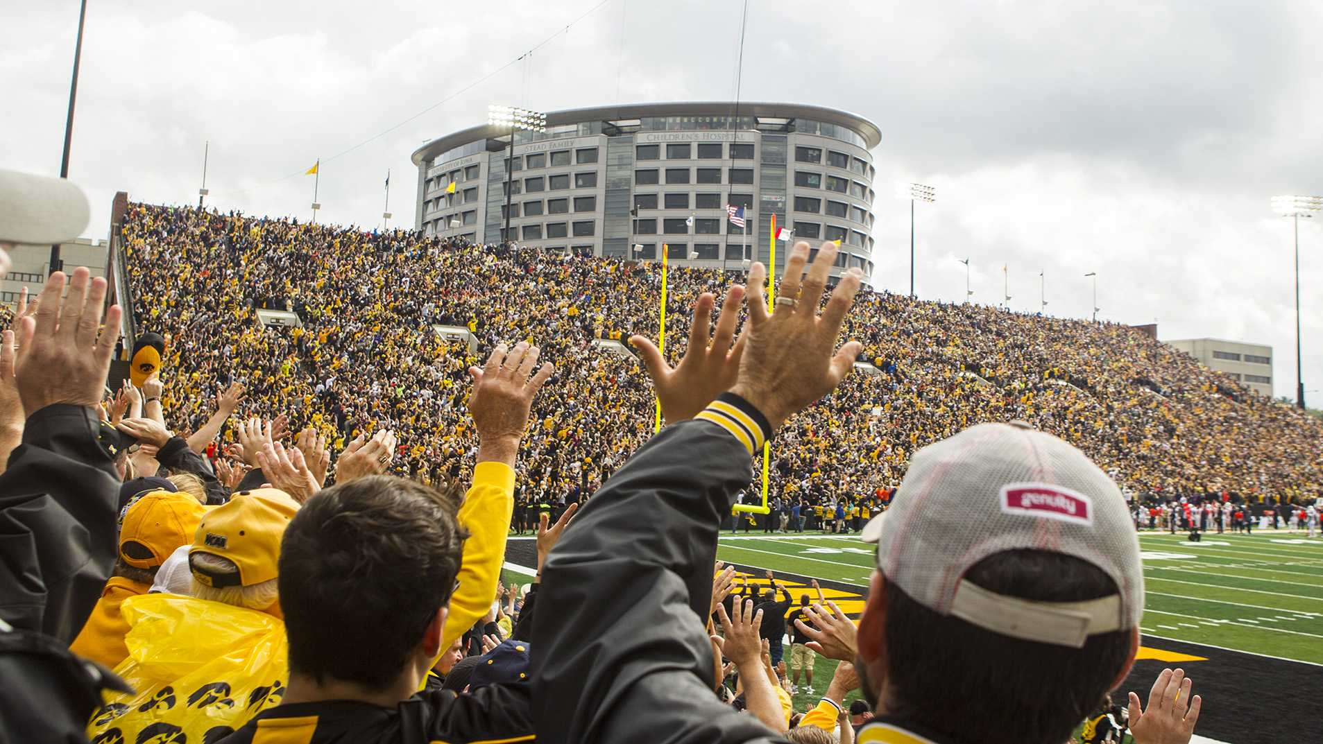 Iowa fans wave to children in the Stead Family Children's Hospital after the first quarter during an NCAA football game between Iowa and Illinois in Kinnick Stadium on Saturday, Oct. 7, 2017.  The Hawkeyes defeated the Fighting Illini, 45-16. (Joseph Cress/The Daily Iowan)